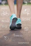 Piedi della donna in scarpe da tennis con le icone di sport Fotografia Stock