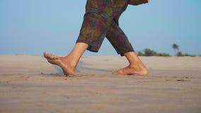 Piedi della donna senior attiva che pratica 'chi' del tai relativo alla ginnastica sulla spiaggia sabbiosa archivi video