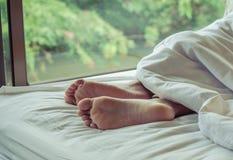 Piedi della donna sul letto Fotografie Stock Libere da Diritti