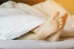 Piedi della donna sul letto bianco Immagine Stock Libera da Diritti