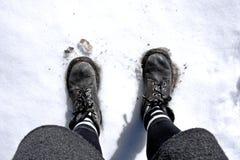 Piedi della donna sulla neve con luce solare dall'angolo alto immagini stock libere da diritti