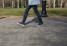 Piedi della gente che cammina in scarpe di sport gi? la via un giorno soleggiato immagini stock