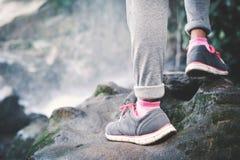 Piedi della ragazza dei pantaloni a vita bassa che camminano nel fondo della cascata Immagine Stock