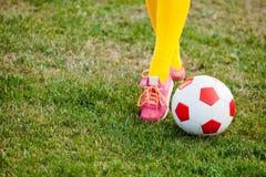 Piedi della ragazza sul campo di football americano con la fine della palla su fotografia stock