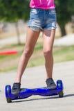 Piedi della ragazza sul hoverboard blu Fotografia Stock Libera da Diritti