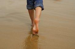 Piedi della signora che camminano sulla sabbia Immagine Stock
