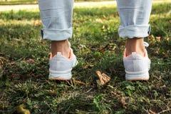 Piedi delle donne nello stile urbano delle scarpe da tennis leggere fotografia stock libera da diritti