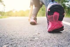 Piedi di donne che corrono sulla strada per salute Immagini Stock