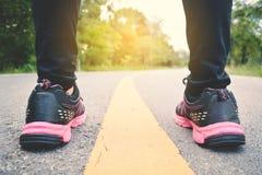 Piedi di donne che corrono sulla strada per salute fotografia stock