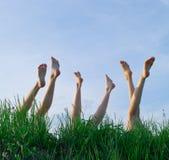 piedi di erba delle ragazze che pone prendere il sole Fotografie Stock Libere da Diritti