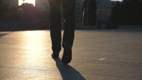 Piedi di giovane uomo d'affari con una cartella che cammina in via della città Uomo di affari che permuta per lavorare Tipo sicur archivi video