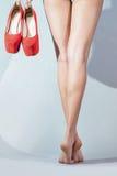 Piedi di ragazza che tiene le scarpe rosse Immagini Stock Libere da Diritti