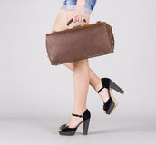 Piedi di ragazza con una valigia a disposizione. Immagini Stock Libere da Diritti