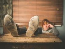Piedi di riposo della donna sulla tavola Fotografia Stock