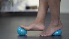 Piedi di rotolamento femminili sul massaggio della palla, allungante fondo del piede, rilascio di dolore archivi video