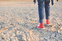 Piedi di scarpa da tennis sulla terra asciutta della crepa Fotografie Stock