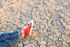 Piedi di scarpa da tennis sulla terra asciutta della crepa Fotografia Stock