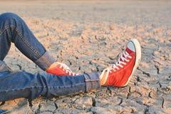 Piedi di scarpa da tennis sulla terra asciutta della crepa Immagine Stock Libera da Diritti