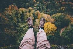 Piedi di selfie sulla scogliera con la vista aerea della foresta di autunno immagine stock