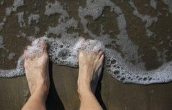 Piedi di un adulto sulla riva di mare e sull'onda Immagine Stock