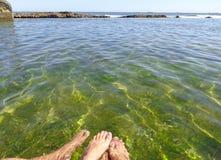 Piedi di una coppia in acqua di mare cristallina con profondità di campo e spazio per pubblicare fotografie stock libere da diritti