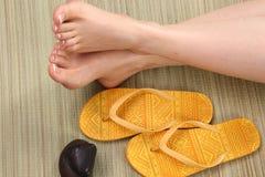 Piedi e flip-flop femminili Fotografia Stock
