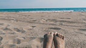 Piedi Femminili Che Prendono Il Sole Sulla Spiaggia Contro Lo Sfondo