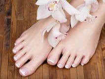 Piedi femminili con il pedicure francese bianco sui chiodi Al salone della stazione termale immagini stock