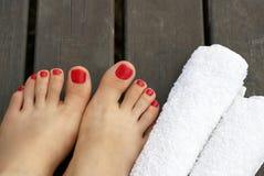 Piedi femminili con un pedicure rosso su un fondo di legno fotografia stock