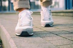 Piedi femminili in scarpe da tennis bianche che camminano sul marciapiede fotografia stock