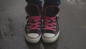 Piedi femminili in scarpe da tennis che si muovono e che posano sull'asfalto bagnato stock footage