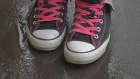 Piedi femminili in scarpe da tennis che si muovono e che posano sull'asfalto bagnato video d archivio
