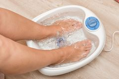 Piedi femminili in un massaggiatore di vibrazione del piede Pediluvio elettrico di massaggio Pedicure e cura dei piedi fotografia stock libera da diritti