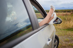 Piedi femminili in una finestra di automobile Immagine Stock