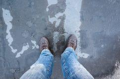 Piedi maschii che stanno sulla pozza congelata con ghiaccio sottile immagini stock