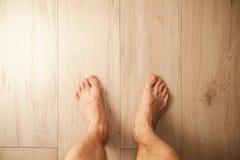 Piedi maschii di supporto sul pavimento di legno immagini stock