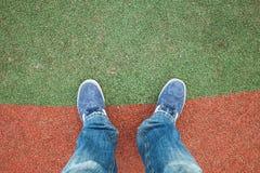 Piedi maschii in jeans e scarpe da tennis su uno stadio fotografia stock libera da diritti