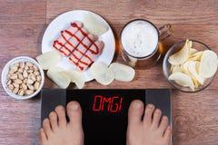 Piedi maschii sulle scale digitali con il omg di parola sullo schermo Birra e piatti con le salsiccie degli alimenti industriali, Fotografia Stock