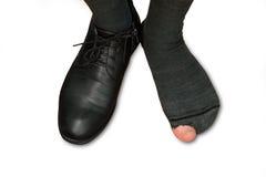Piedi maschii in una scarpa ed in calzini lacerati isolati su fondo bianco Immagini Stock Libere da Diritti