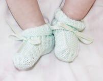 Piedi minuscoli del bambino in babbucce Fotografia Stock