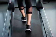 Piedi muscolari femminili in scarpe da tennis che corrono sulla pedana mobile alla palestra Immagini Stock