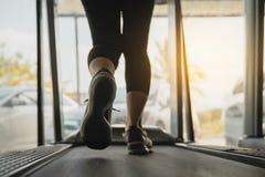 Piedi muscolari femminili in scarpe da tennis che corrono sulla pedana mobile alla palestra, corpo più basso alla parte delle gam fotografie stock