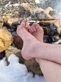 Piedi nudi che scaldano ad un fuoco di accampamento in inverno Fotografie Stock Libere da Diritti