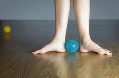 Piedi nudi del ballerino di balletto sul pavimento di legno vicino ad una palla di massaggio fotografia stock