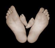 Piedi nudi del bambino con i piedi della mamma fotografie stock