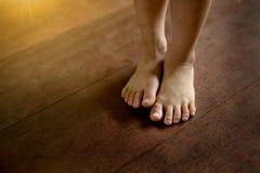 Piedi nudi del ` s dei bambini sul pavimento di legno Immagine Stock