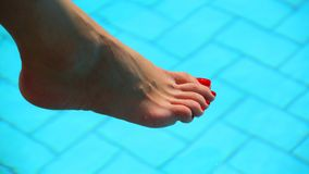 Piedi nudi della donna sopra l'acqua della piscina Fotografie Stock Libere da Diritti