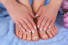 Piedi nudi e mani della donna con la lucidatura di unghie francese sull'asciugamano blu con il fiore rosa in studio immagine stock