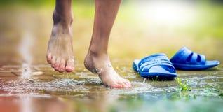 A piedi nudi i piedi del ragazzo e della caviglia in una pozza di fango Fotografia Stock Libera da Diritti