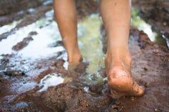 A piedi nudi tramite la strada fangosa Immagini Stock